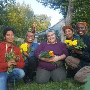 Queer Black and Brown folx smiling holding flowers and plants.